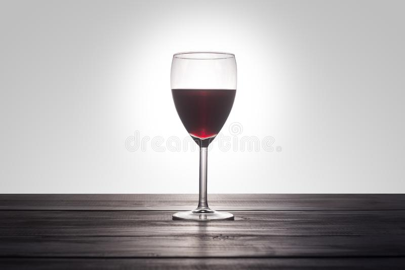 A glass of red wine on a wooden surface royalty free stock photo