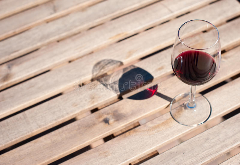 Glass with red wine on a wooden table. Glass with red wine on a wooden board royalty free stock images