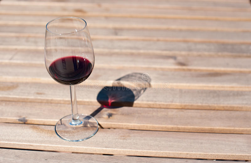 Glass with red wine on a wooden table. Glass with red wine on a wooden board stock photos