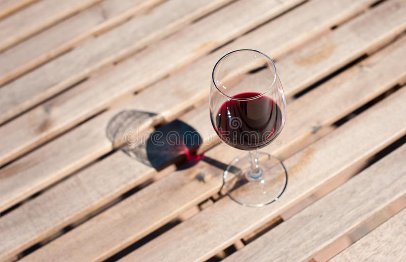 Glass with red wine on a wooden table. Glass with red wine on a wooden board royalty free stock photography