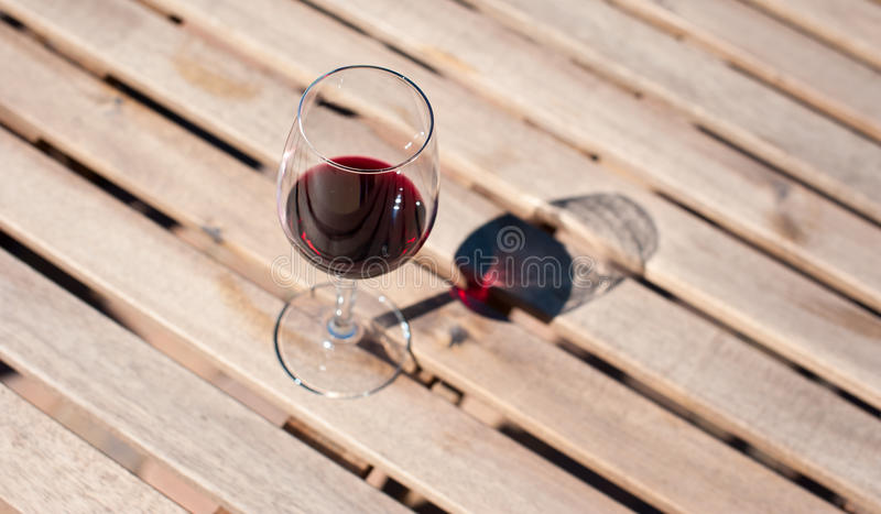 Glass with red wine on a wooden table. Glass with red wine on a wooden board stock images