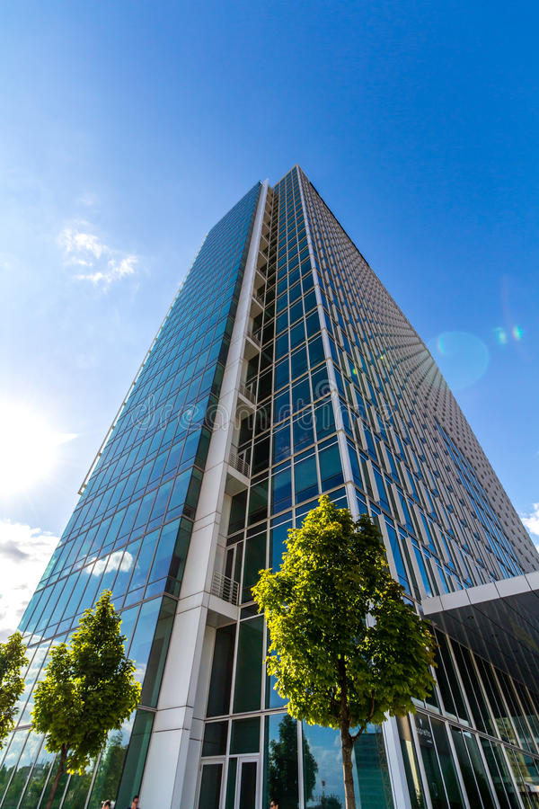 Glass reflekterande kontorsbyggnader mot blå himmel arkivbild