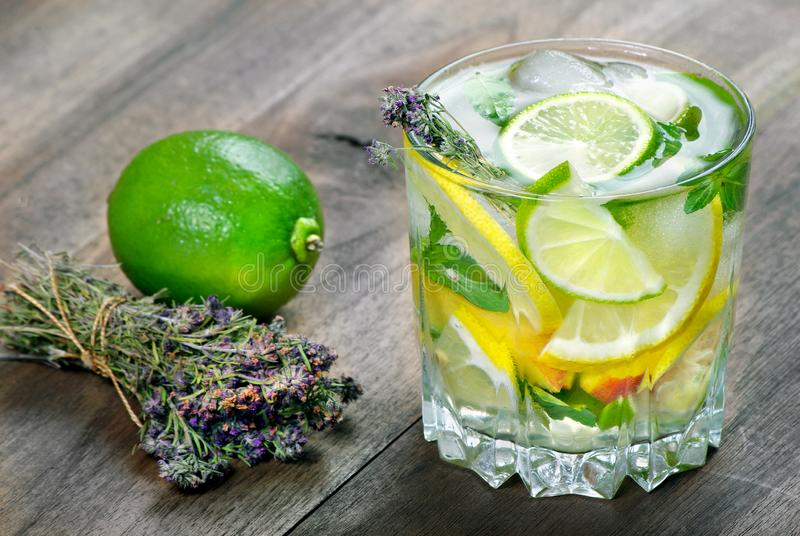 Glass of refreshing drink. glass of cold water with ice, thyme, mint and lemon on a wooden table. close up stock photos