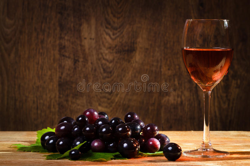 Glass of rose wine with dark grapes stock photo