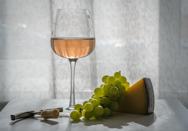 Glass of rose wine on the table, next to green grapes, hard cheese, corkscrew with cork. Close-up, backlight royalty free stock photography