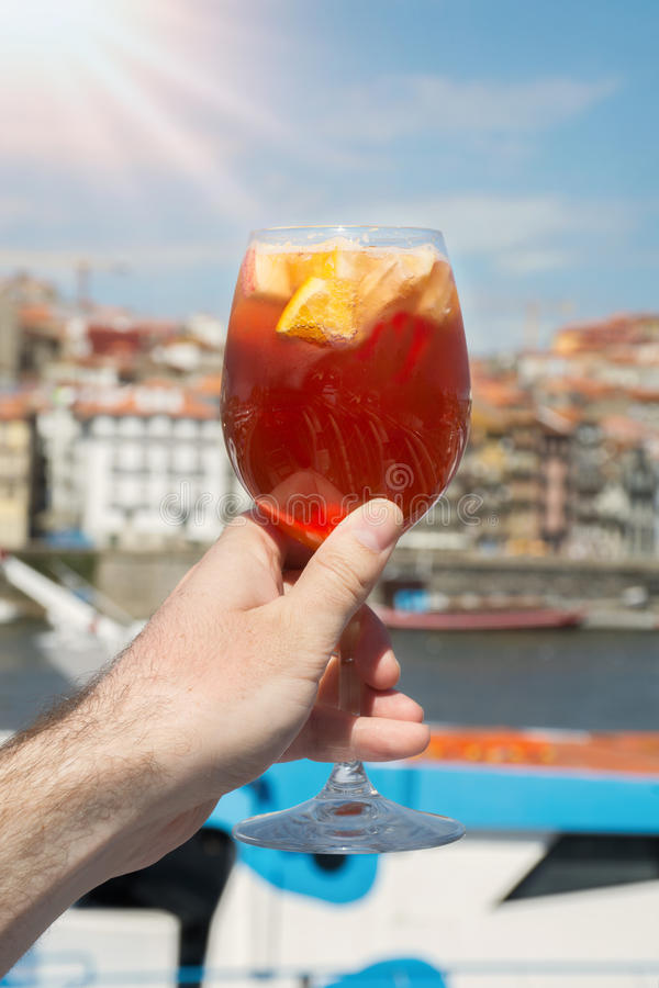 A glass of sangria in hand against the background of the Douro R royalty free stock photos