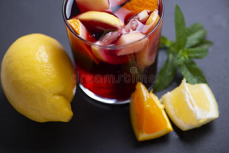 Glass with sangria next to a lemon, orange, and mint leaf on black slate base. Typical Spanish drink. Glass with sangria next to a lemon, orange, and mint leaf stock photography