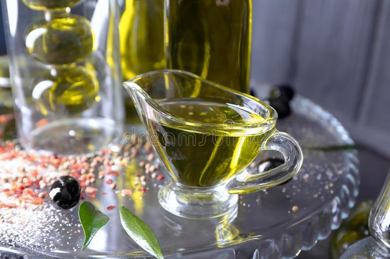 Glass sauce boat with olive oil on table stock images