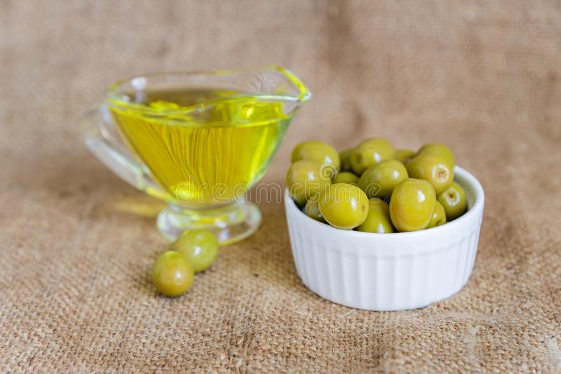 Glass sauceboat with extra virgin olive oil and fresh green olives in white ceramic bowl on  burlap cloth background.  stock photo