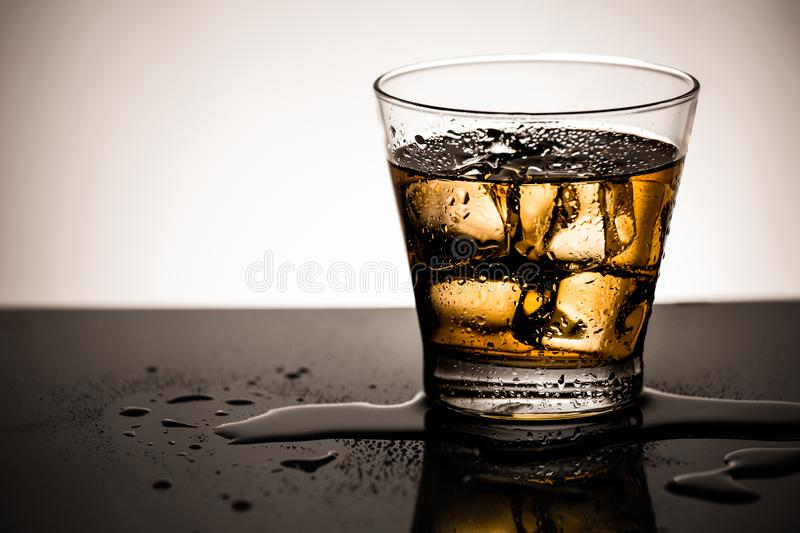 Glass of scotch whiskey with ice cube,Cold beverage of alcohol and reflection on glass stock photos