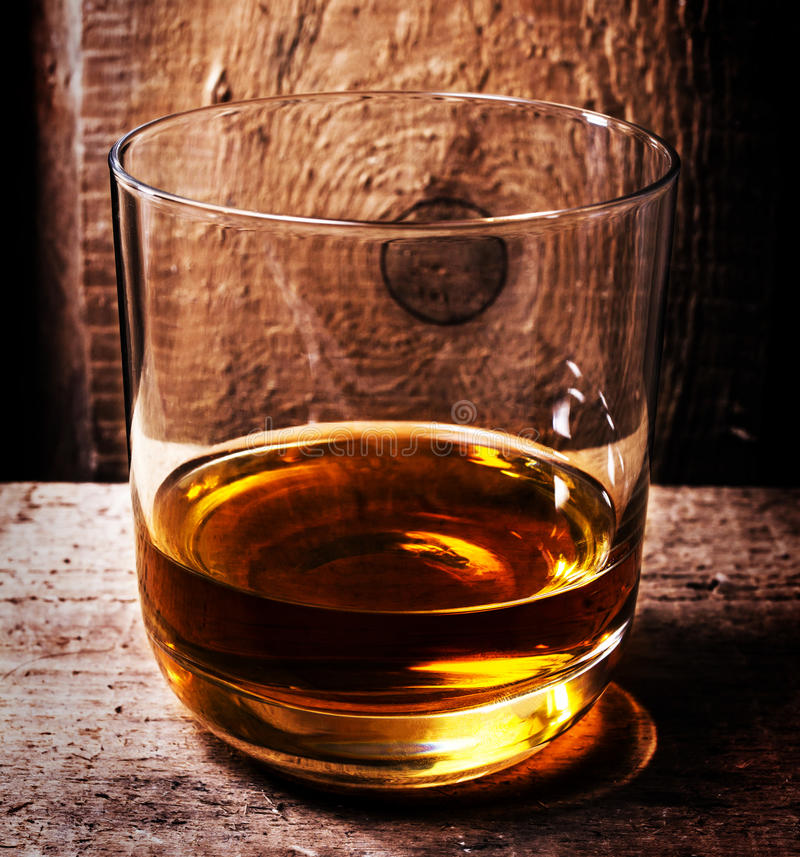 Glass of Scotch whiskey on old wooden background. An old and vintage oak countertop and glass of hard liquor. royalty free stock photos