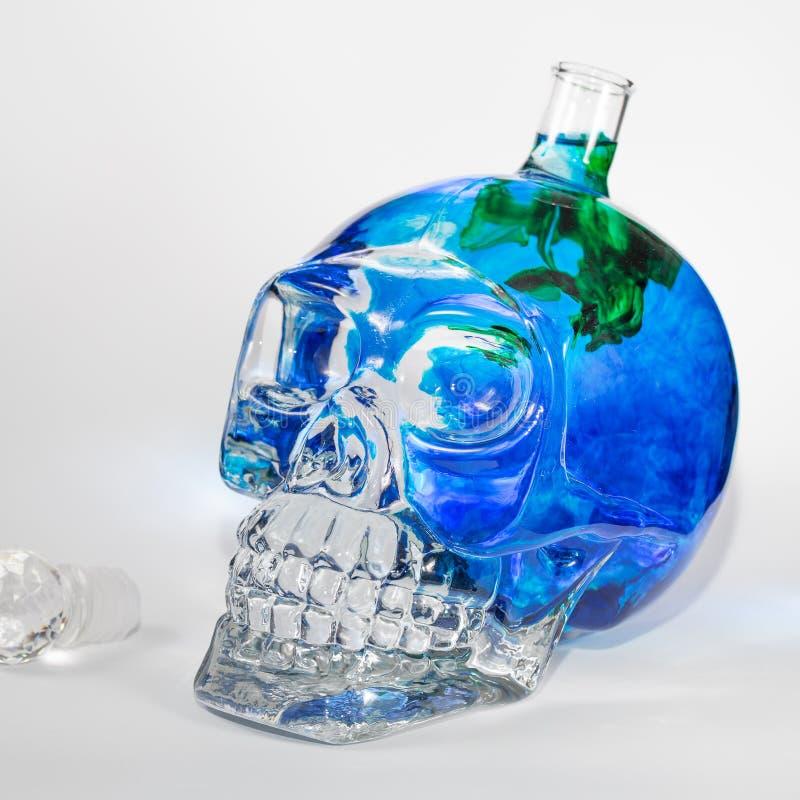 Glass skalle med färgpulverdroppar fotografering för bildbyråer