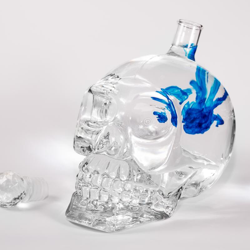 Glass skull with ink drops stock photo