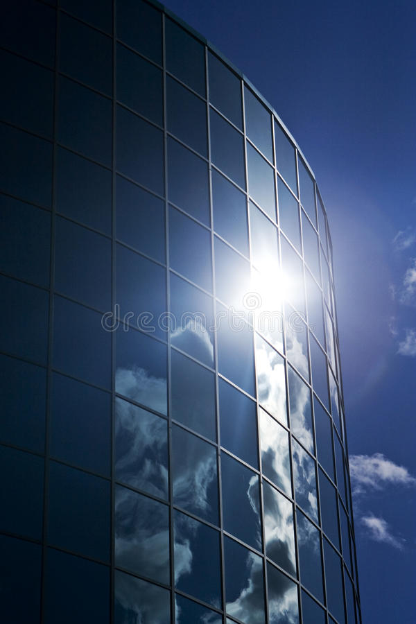 Glass Skyscraper Building. Glass skyscraper front with a reflection of the sky and clouds stock photos