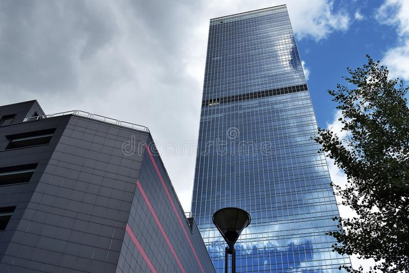 The clouds above the skyscraper are reflected in the glass stock photos