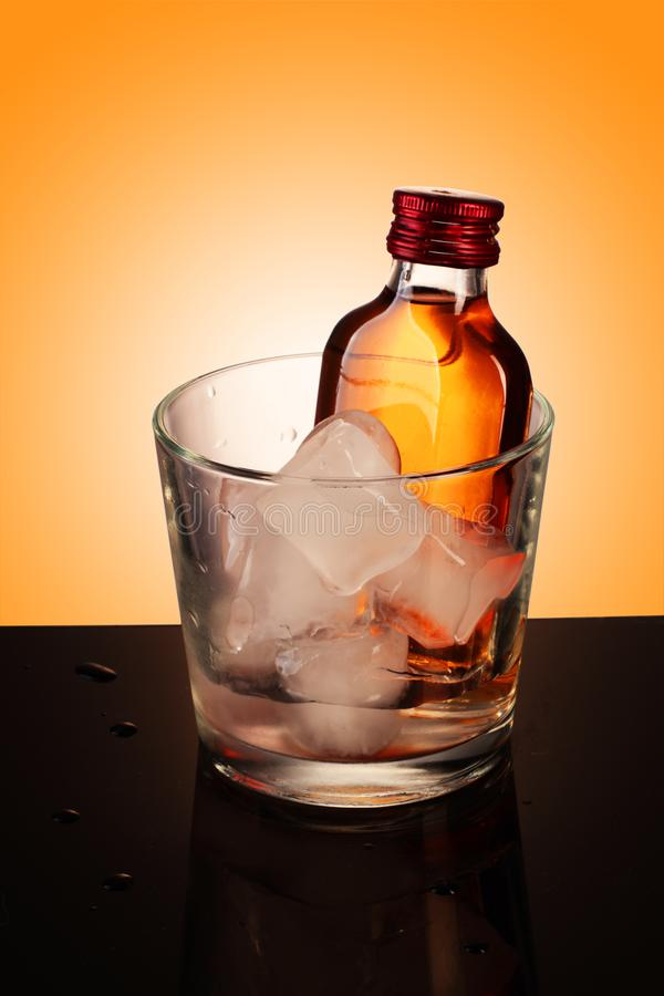 A glass with a small bottle of vodka royalty free stock images