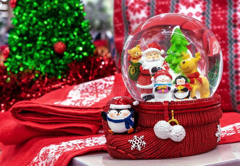 Glass snow globe with Santa Claus, deer, penguin, christmas tree and snowman inside royalty free stock photos