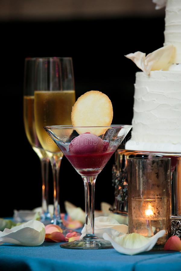 A glass with sorbet and a cookie with champagne glasses and a wedding cake in the background served during a fancy wedding royalty free stock photos