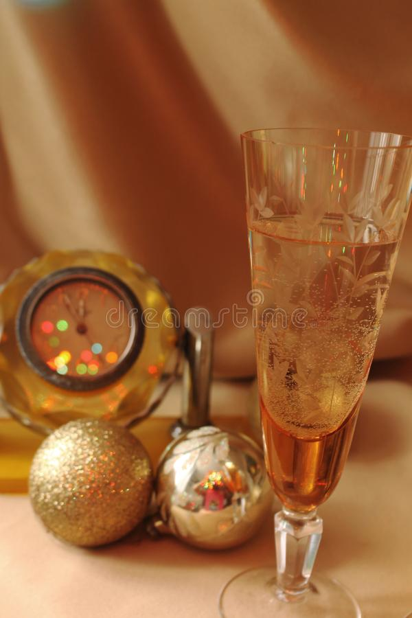 A glass of Soviet champagne in a glass retro glass on the background of yellow mechanical watches of the USSR and decorations for stock photos