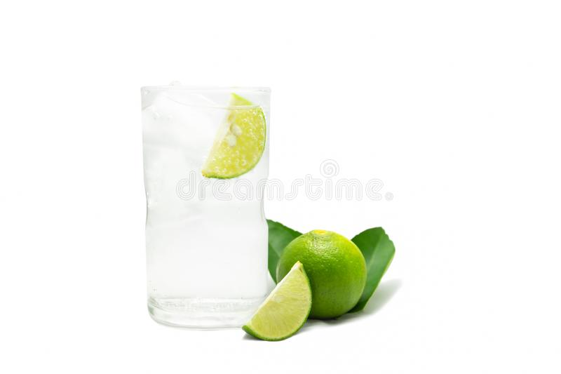 Glass of sparkling water soda with ice and lime slice on white background. royalty free stock photo