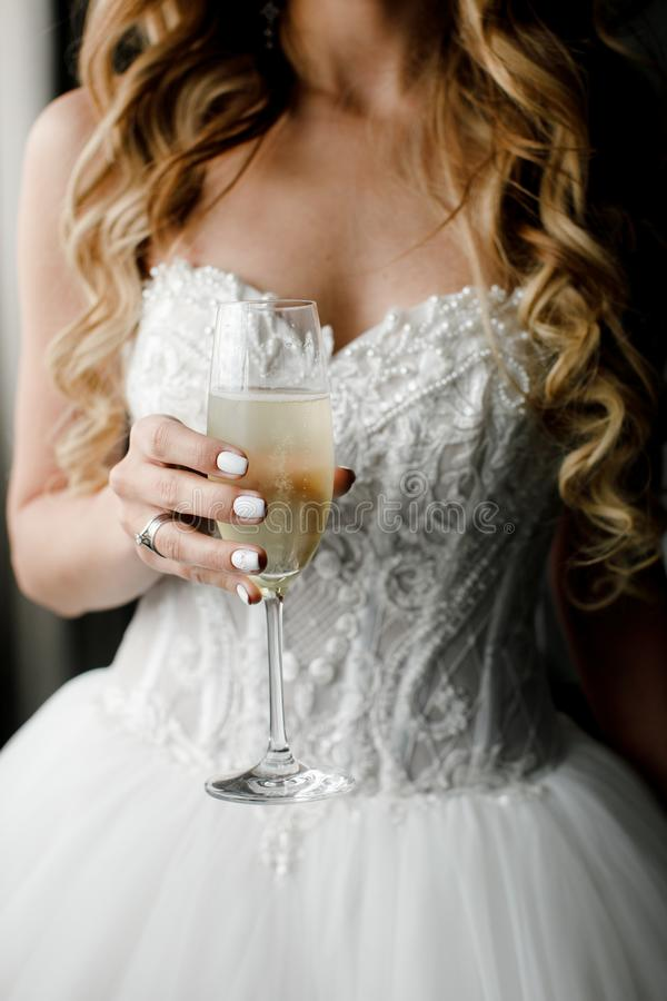 A glass of champagne in the hands of the bride stock photography