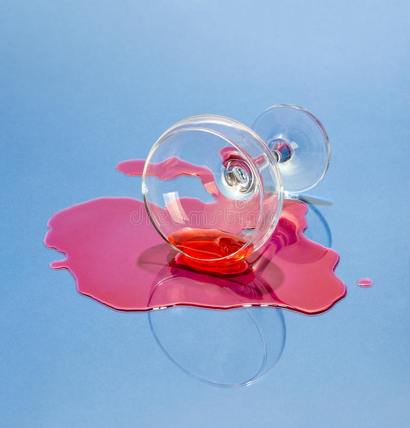 A glass and spilled liquor on a light blue background. Art photo stock photos