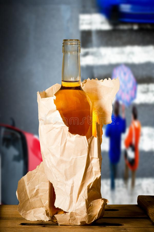 Glass of spirits in the paper bag. In the street royalty free stock image