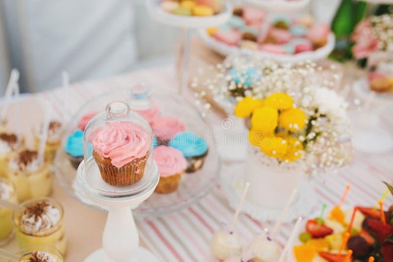Glass ställning med locket med den rosa muffin bredvid blommor och andra sötsaker på godisstång royaltyfri fotografi