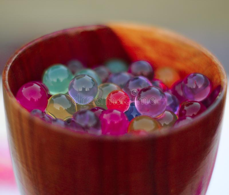 Jelly balls growing in water on wooden glass. stock image