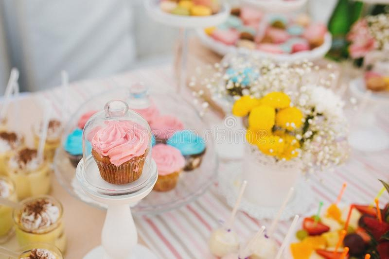 Glass stand with lid with pink cupcake next to flowers and other sweets on candy bar royalty free stock photography