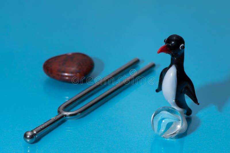 Glass statyett av en gullig liten pingvin med en röd näbb arkivbilder