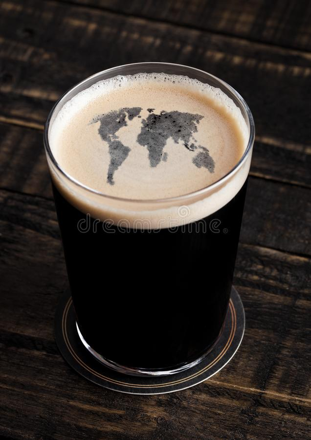 Glass of stout beer top with earth shape stock photo