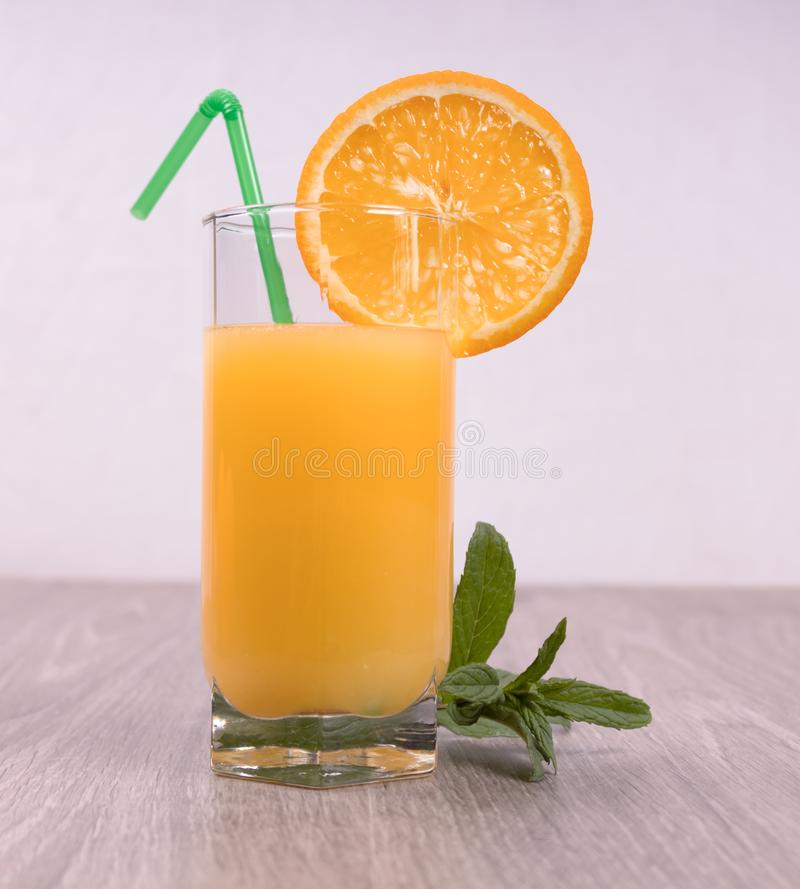 A glass with a straw decorated with an orange slice and mint on a light background royalty free stock images