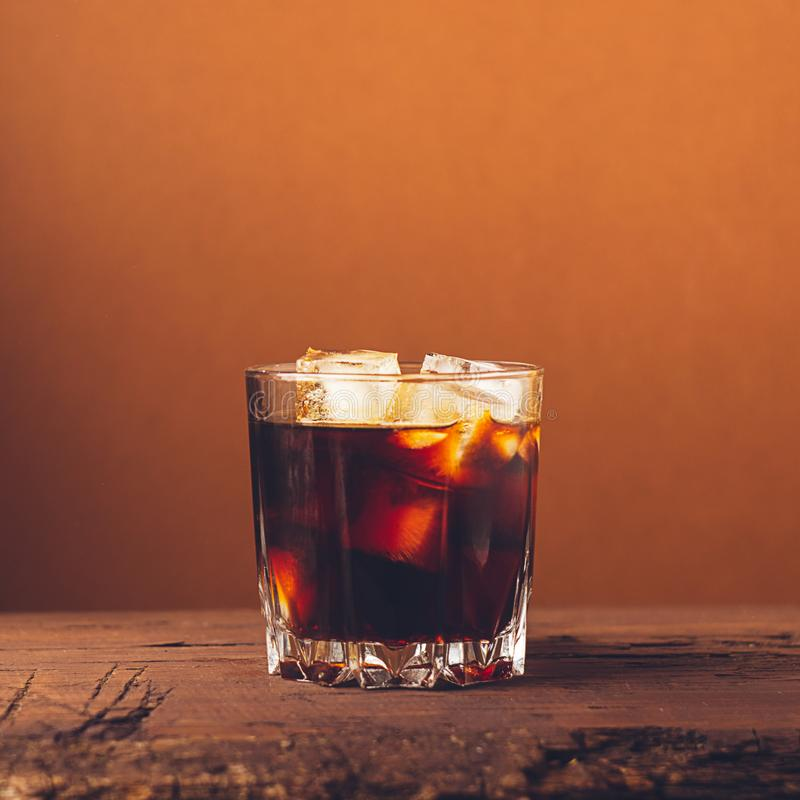A glass of strong alcoholic drink whiskey brandy on a dark wooden background. Selective focus. Square frame royalty free stock images