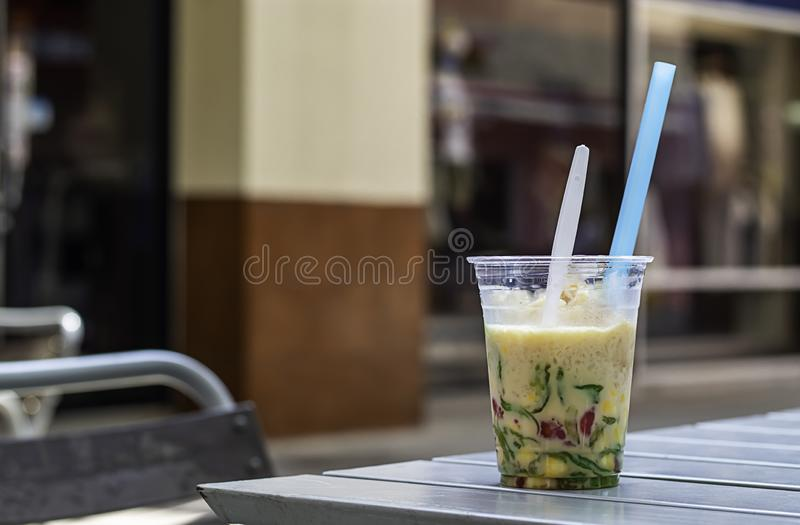 Glass of sweet candy Thailand with ice and coconut milk on table.  stock photos