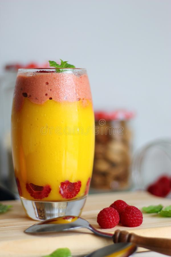 Glass of sweet delicious homemade layered smoothie dessert made from fruits and berries. stock photography