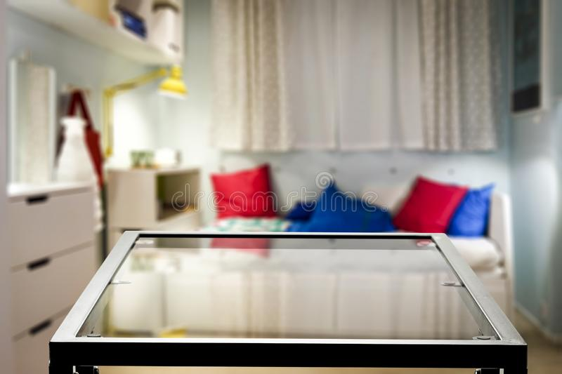 Glass table with blurred cosy white room background. Nice home interior with sofa with colourful armchairs and some furniture stock image