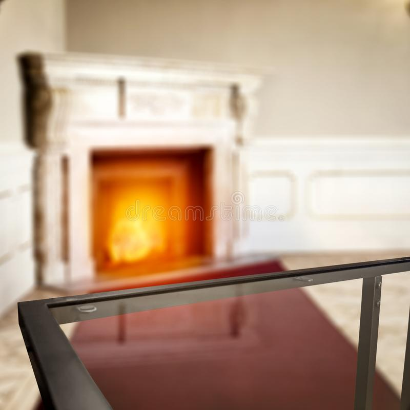 Glass coffee table top with a blurred fireplace and home interior background. Empty space for your products and decoration. Glass table top with a blurred home royalty free stock photo