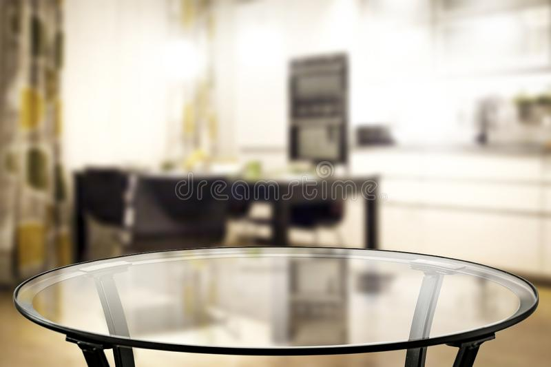 Glass coffee table top with a blurred kitchen and home interior background. Empty space for your products. Glass table top with a blurred home interior royalty free stock photo