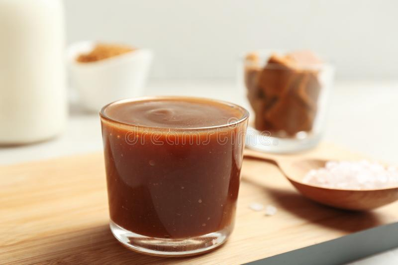 Glass with tasty caramel sauce and spoon. On wooden board royalty free stock photography