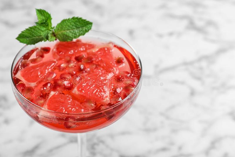 Glass of tasty refreshing with grapefruit and pomegranate on white marble table, closeup. Space for text. Glass of tasty refreshing cocktail with grapefruit and royalty free stock photo