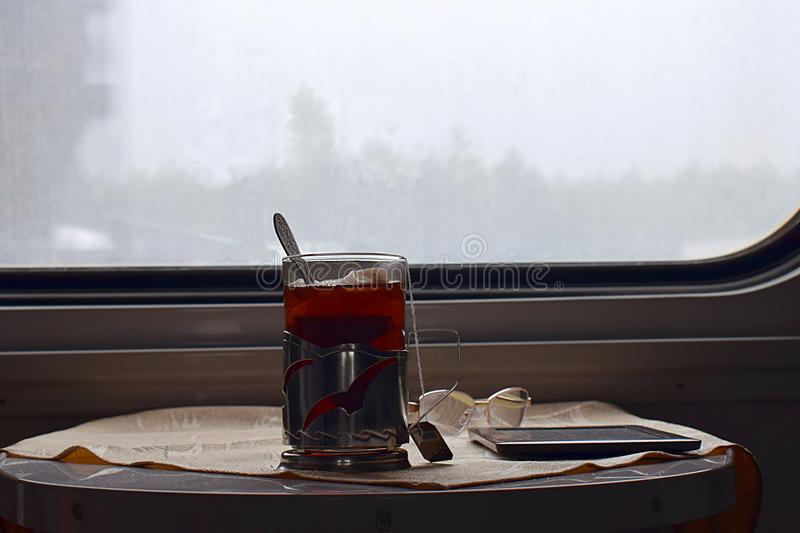 A glass of tea, an electronic book and glasses in a train car. royalty free stock images