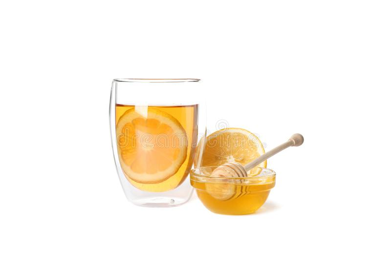 Glass of tea with lemon, honey and dipper isolated on white royalty free stock image