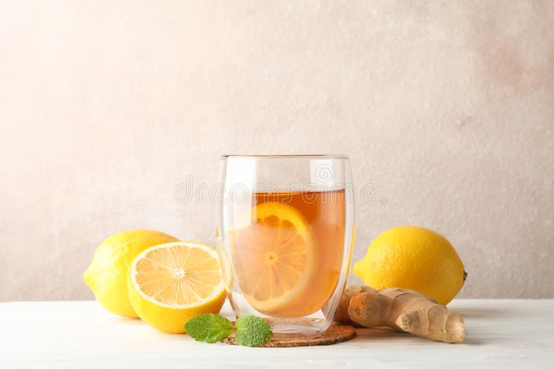 Glass of tea with lemon, mint, honey, dipper and ginger on wooden background stock images