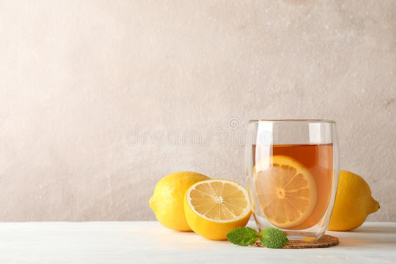 Glass of tea with lemon, mint, honey, dipper and ginger on wooden background royalty free stock photo