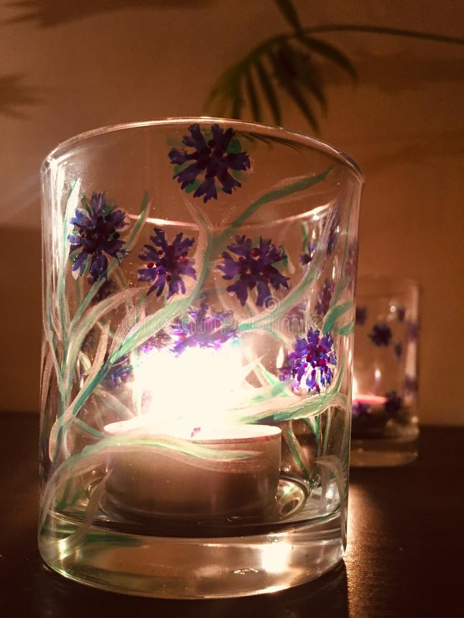 Glass tea light holder painted with corn flowers stock photos