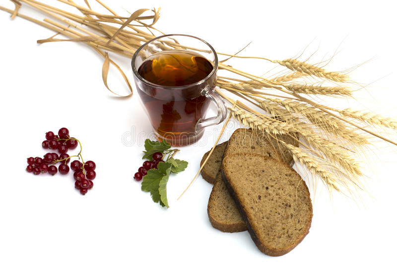 Glass of tea, wheat about fields and bread royalty free stock image