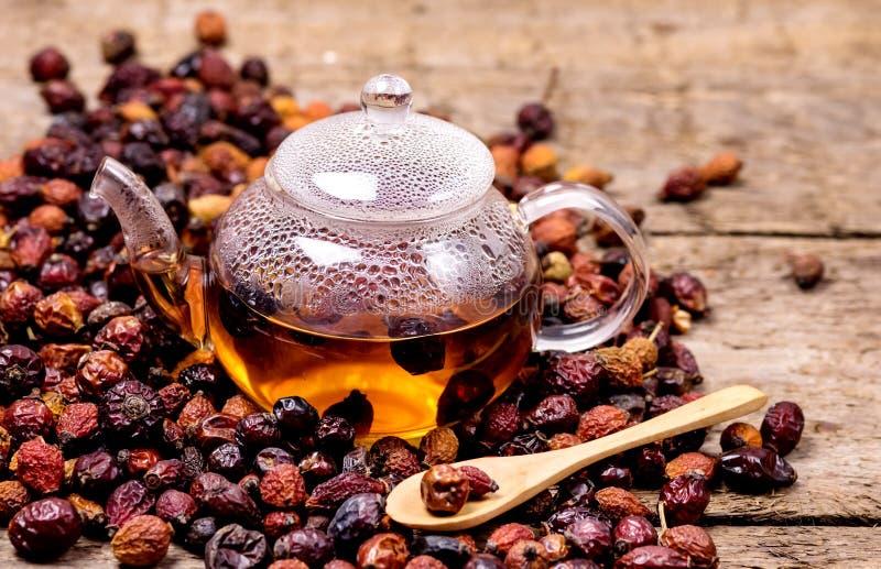 Glass Teapot av örtte Rose Tea med torkade rosehips, typsnitt Rosa Canina Hips Hot Drink of Medicinal Plants and Herbs Wooden royaltyfri bild