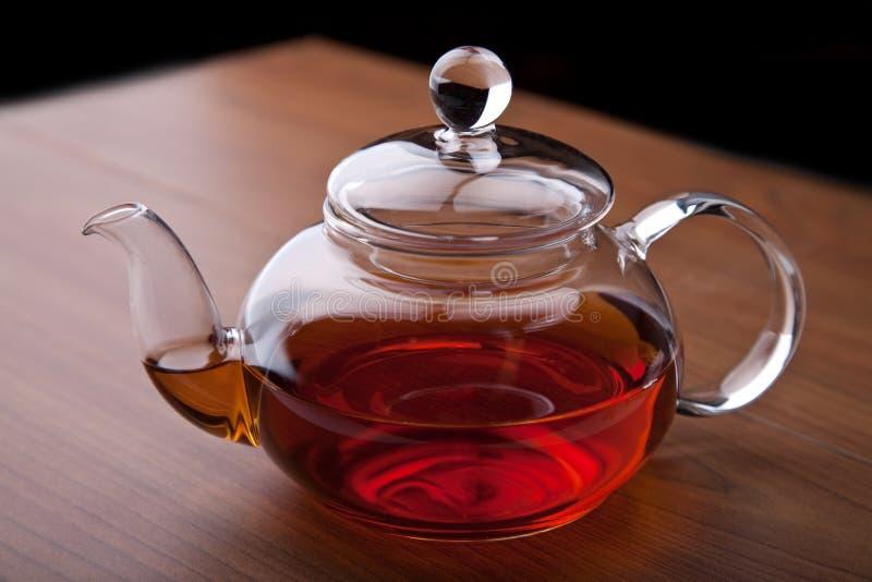 Glass teapot with black tea stock image