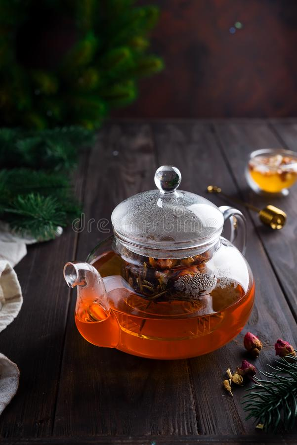 Glass teapot with freshly brewed herbal tea and honey on a wooden background. Christmas or hot winter drink to warm. stock photography